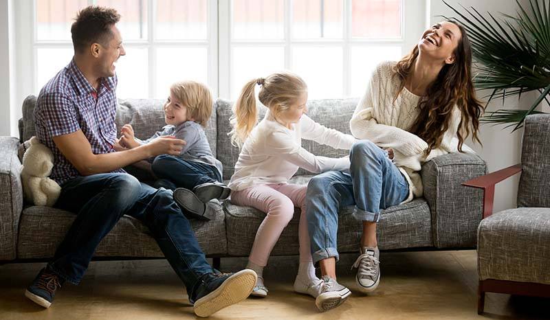 Young Family Having Fun Sitting Together on Sofa in Cozy Home Indoors