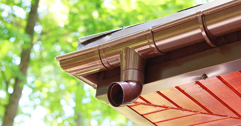 Modern Roof of House with Plastic Rain Gutter on Beautiful Green Vegetation Background